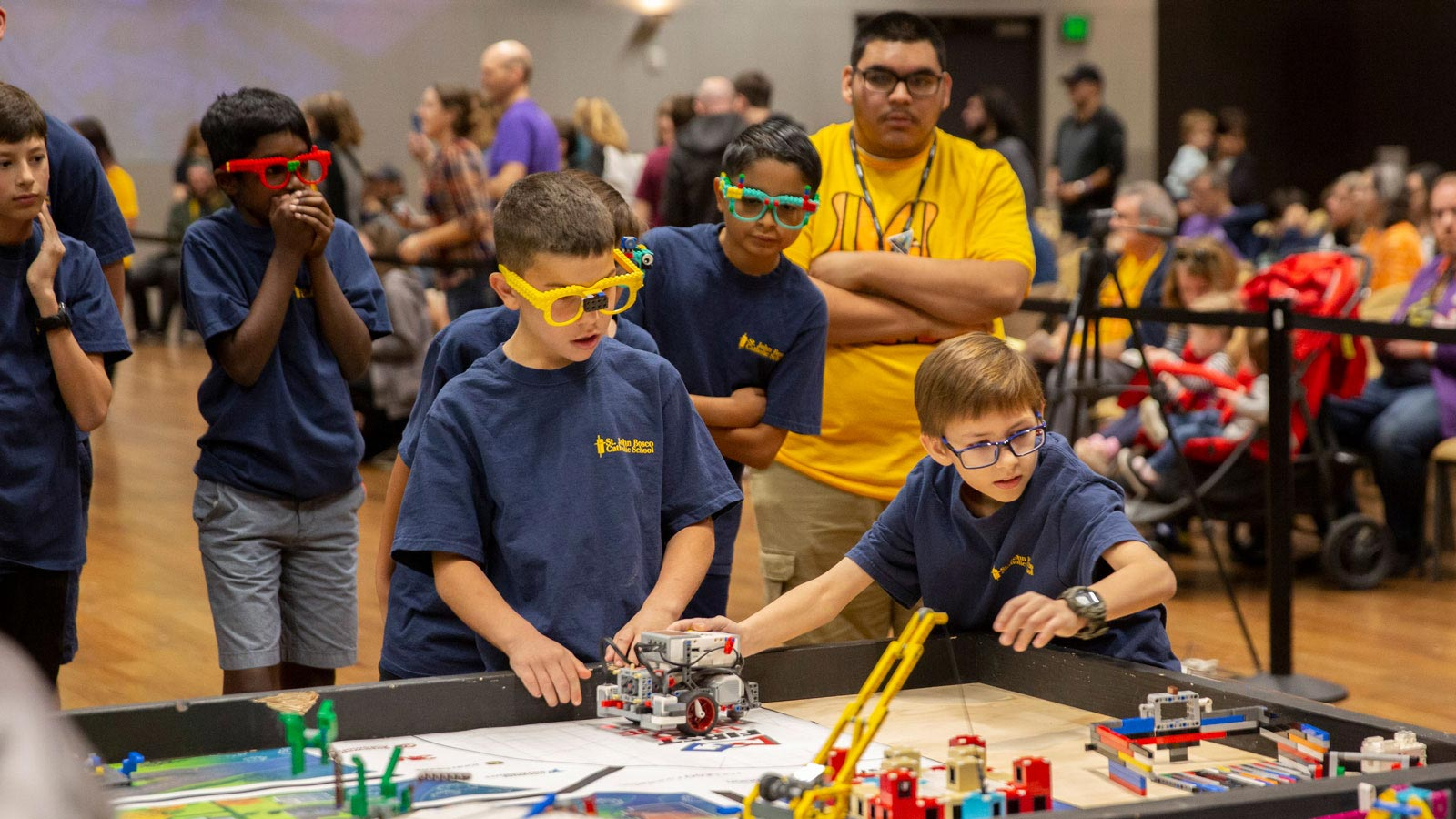 Elementary-age boys using a LEGO robot in competition.