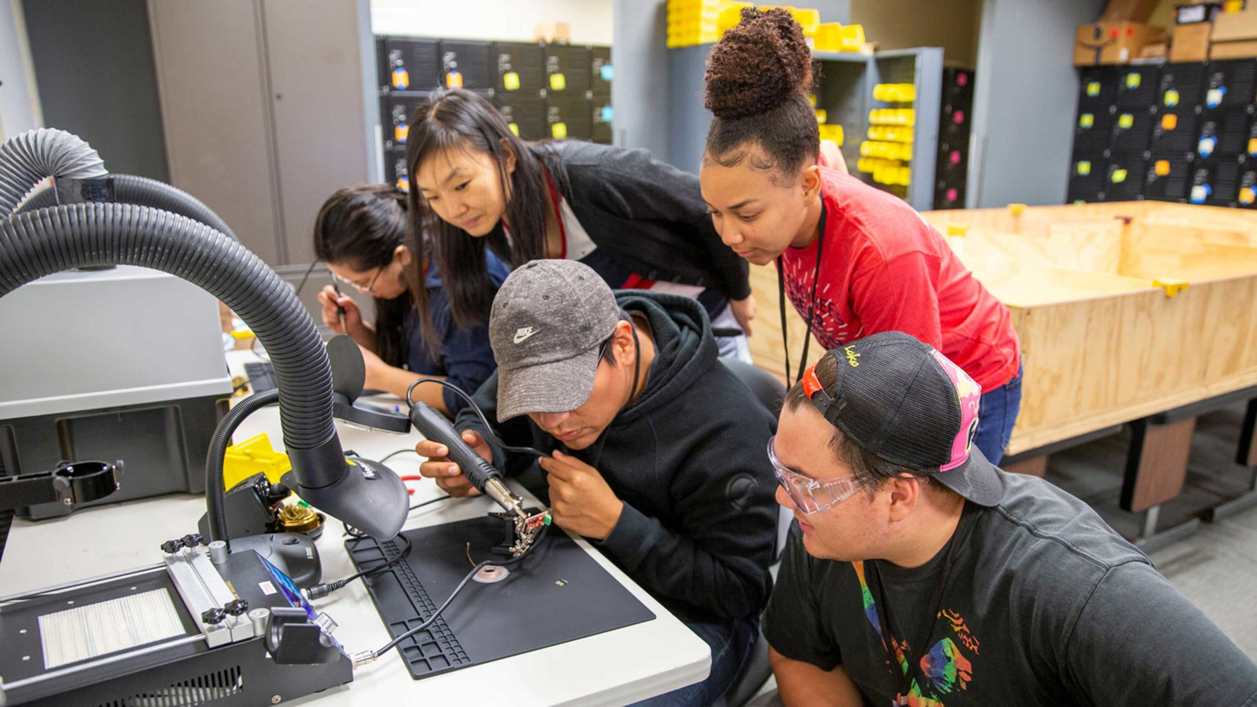 Five undergraduates work together soldering a small robot component at the ASU 2019 Robo Hackathon