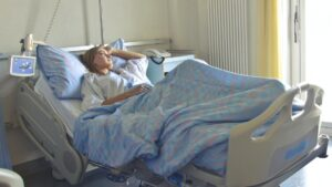 A woman rests in a hospital bed with no visitors