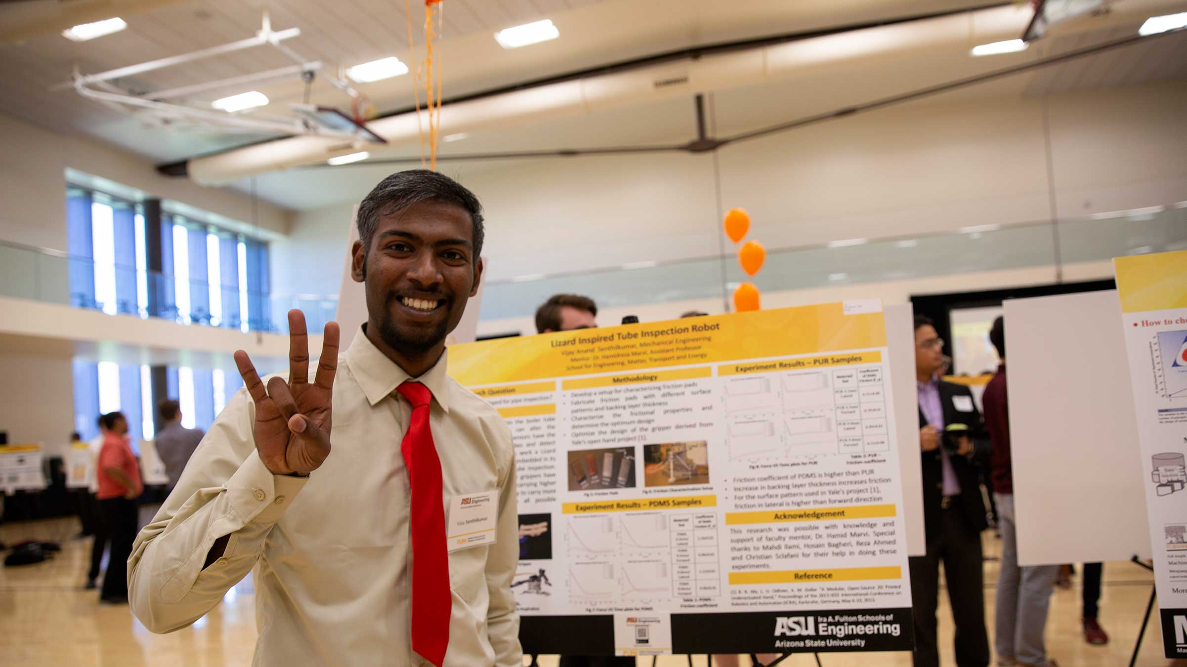 An international student from India stands by his research poster at FURI