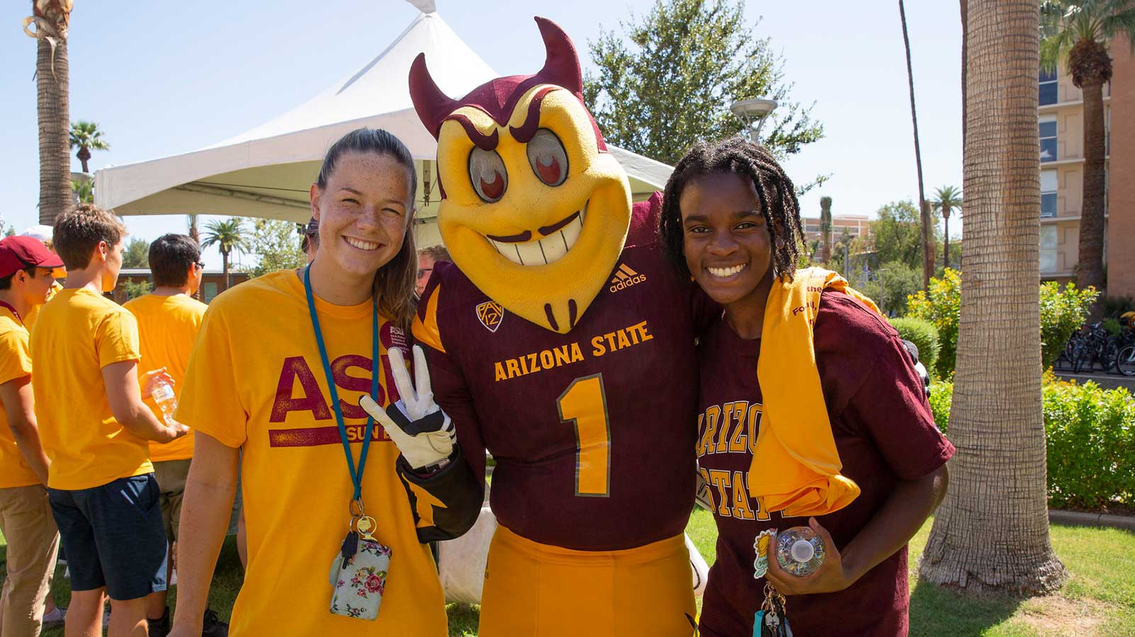 Two students standing with Sparky during the Fall Welcome resources fair.