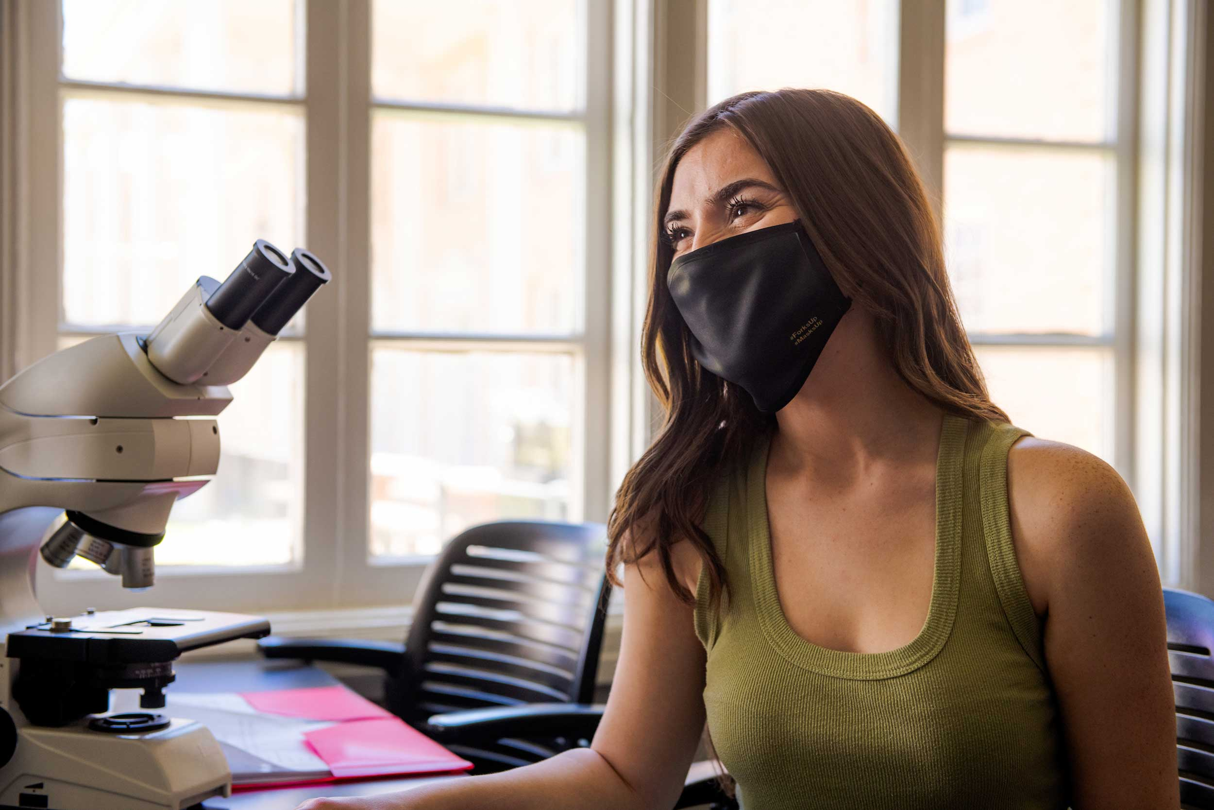 A student wearing a mask sits at a microscope