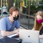 Two students wearing masks while sitting outside and sharing a laptop.