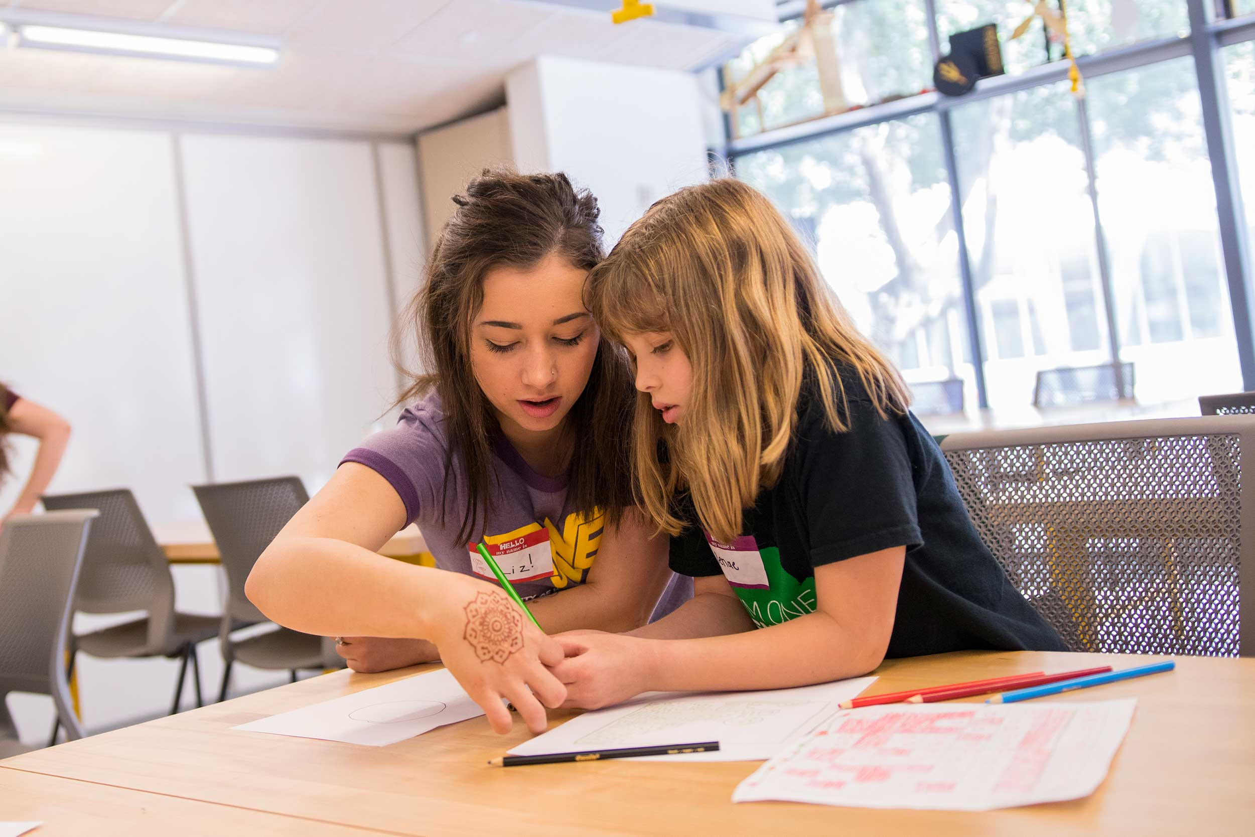 Elizabeth Jones helps an elementary-aged girl with an engineering project