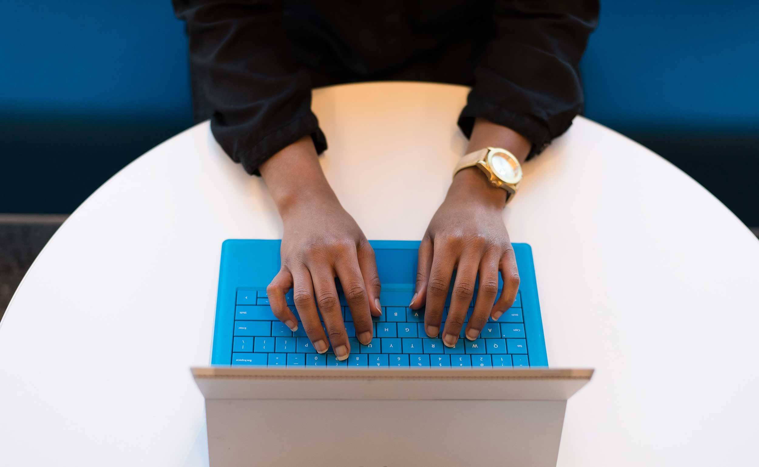 top-down view of a black woman's hands typing on a laptop