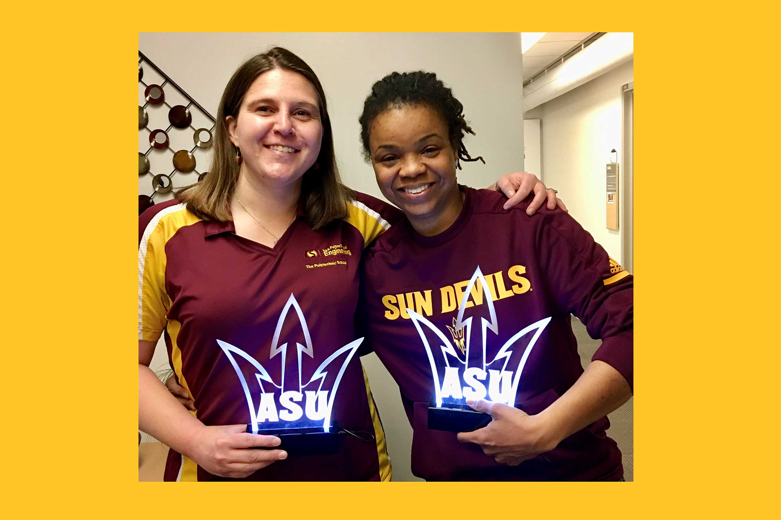 Jennifer Bekki and Brooke Coley stand together, arms around each other, holding their awards from ASU