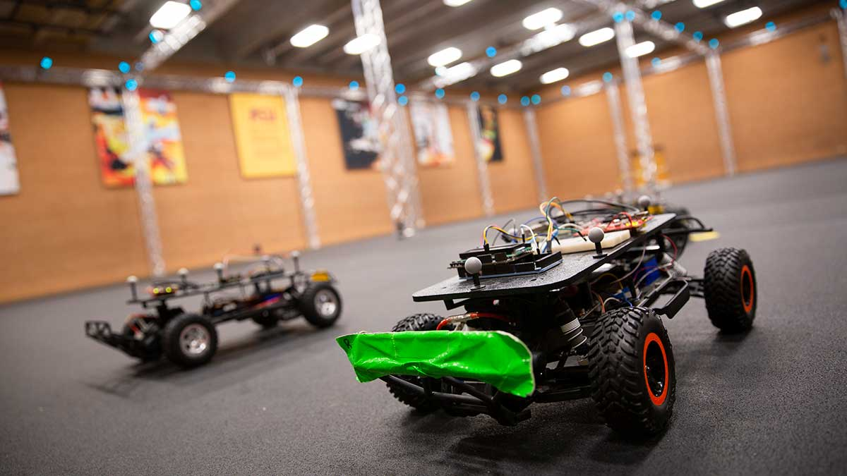 A couple of small, vehicle-like robots on wheels are shown on the floor of the ASU Drone Studio, while small blue sensors are seen in the rafters of the ceiling.