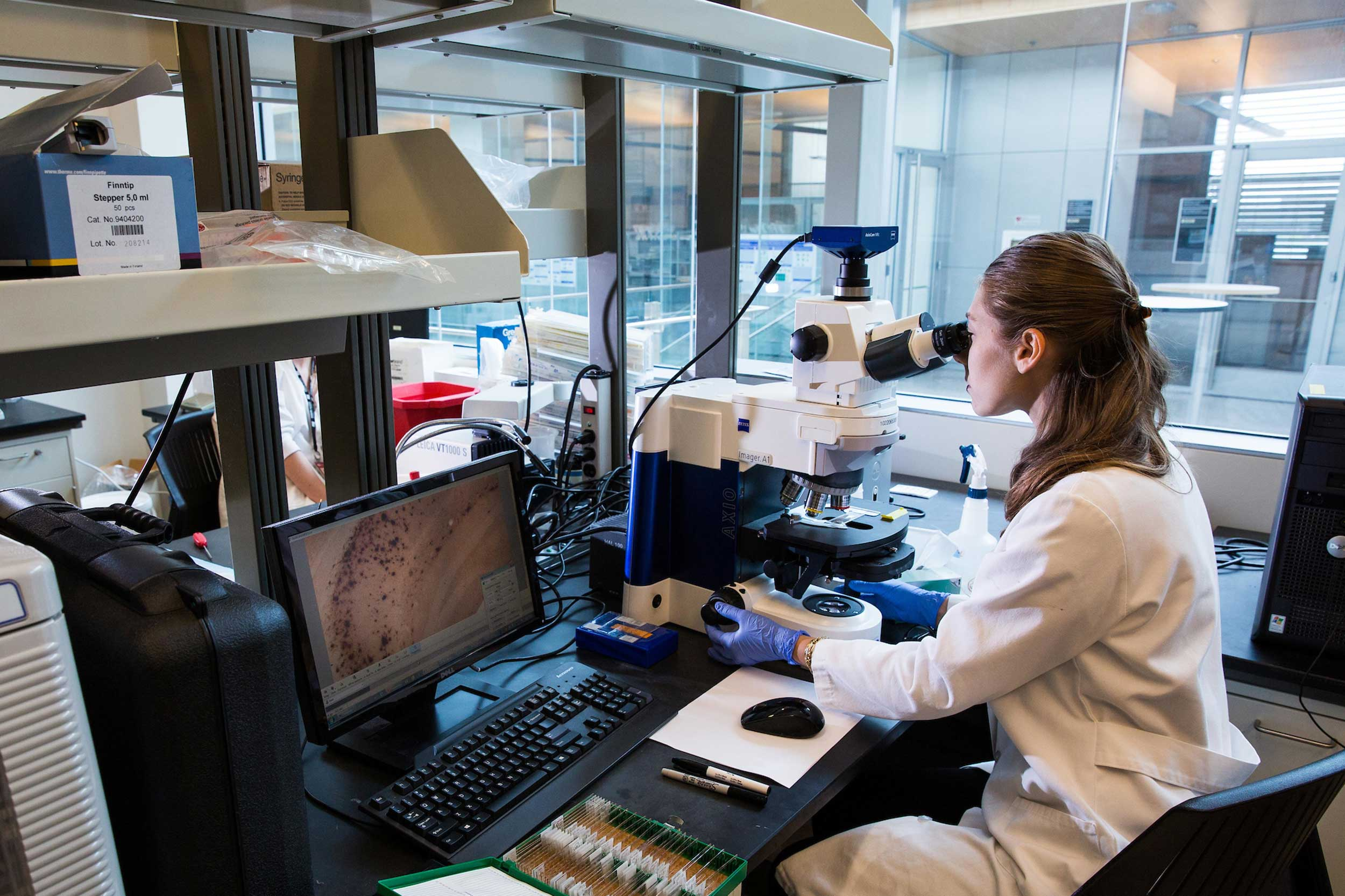 A woman sits at a microscope in a university lab