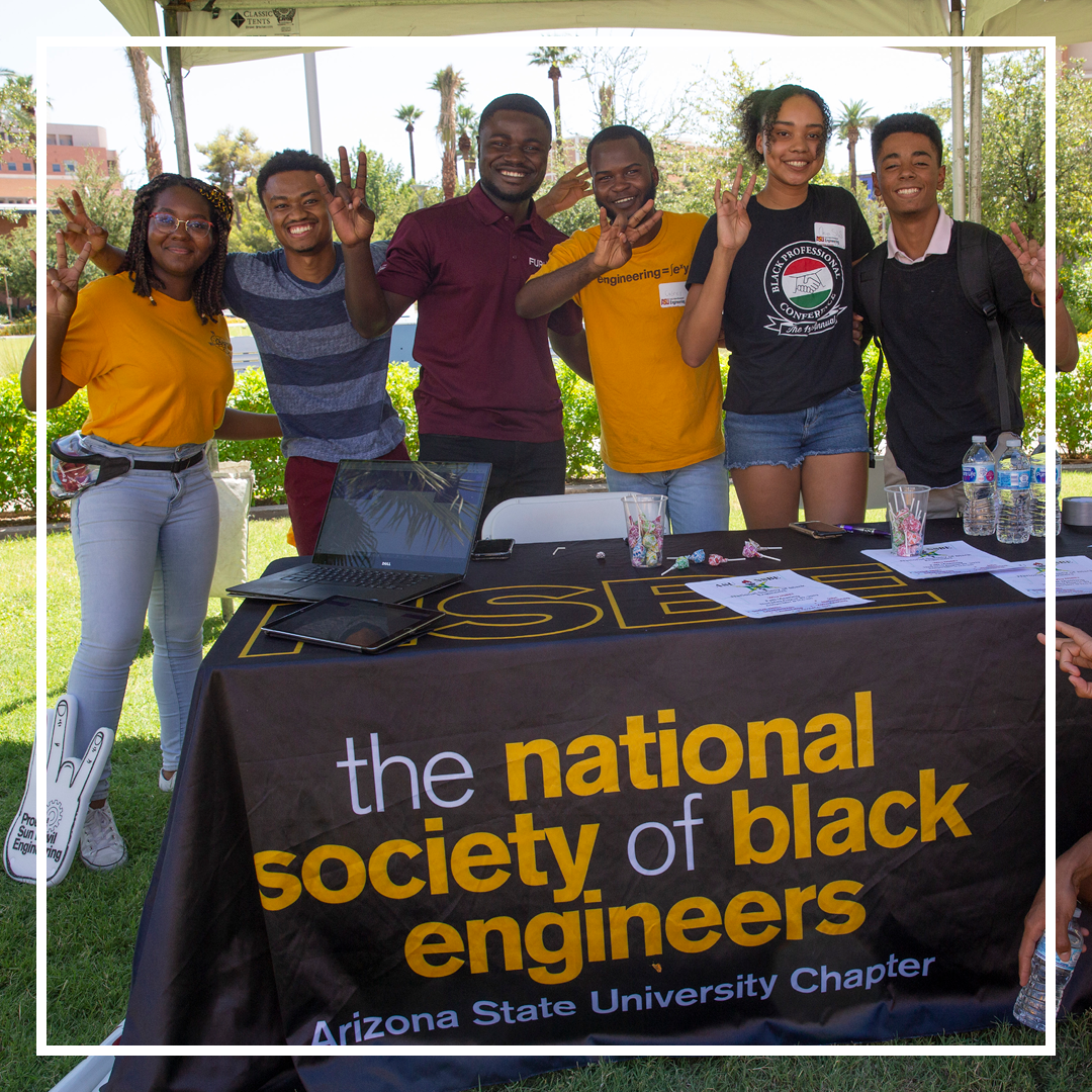 National Society of Black Engineers ASU Chapter members stand together at their table at an event
