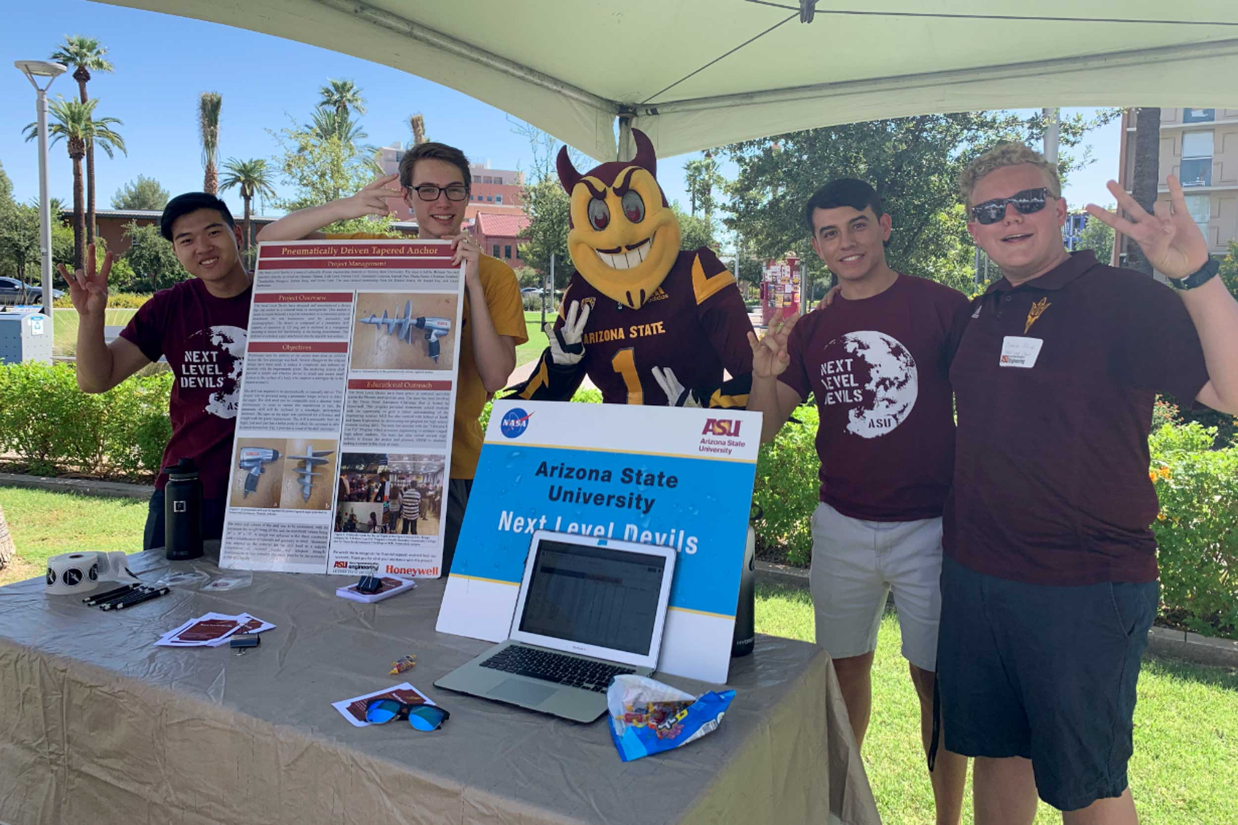 Four Next Level Devils members pose with ASU's mascot Sparky at a 2019 event