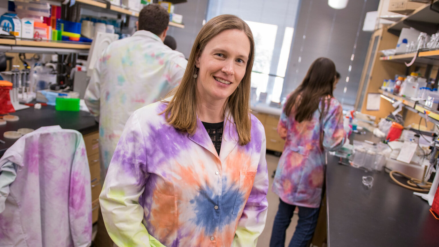 Sarah Stabenfeldt, wearing a tie-dye lab coat, stands in her lab with other researchers