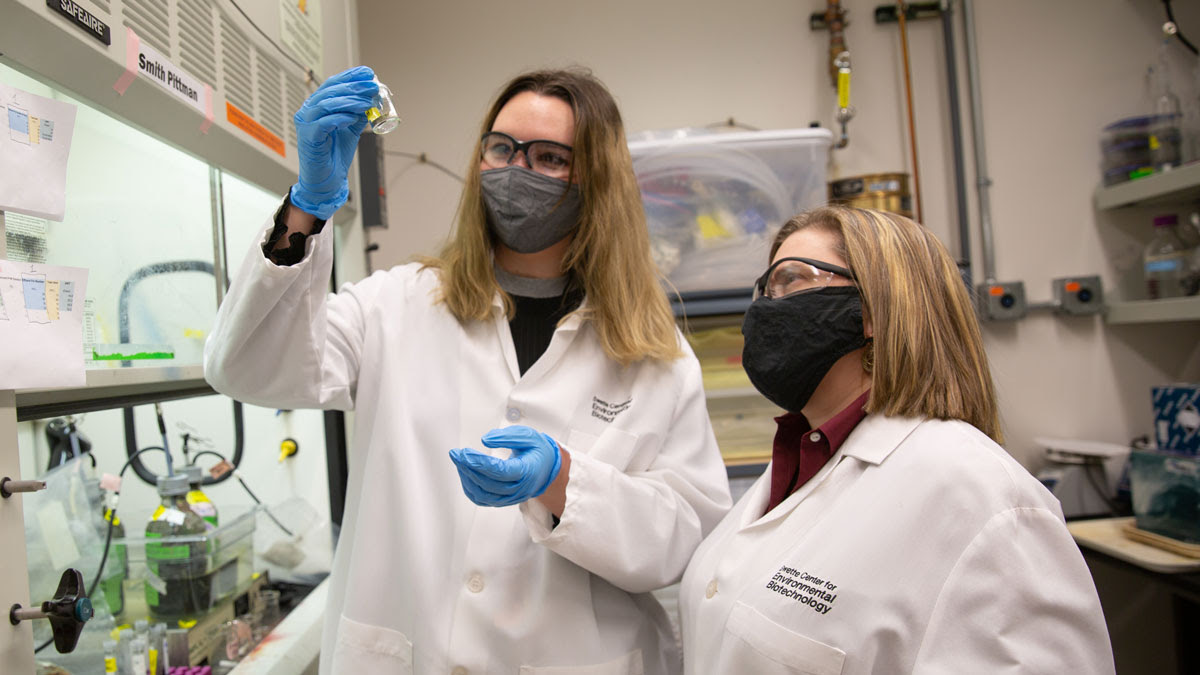 Two student researchers work in a lab wearing lab coats and masks, examining a vial of a substance