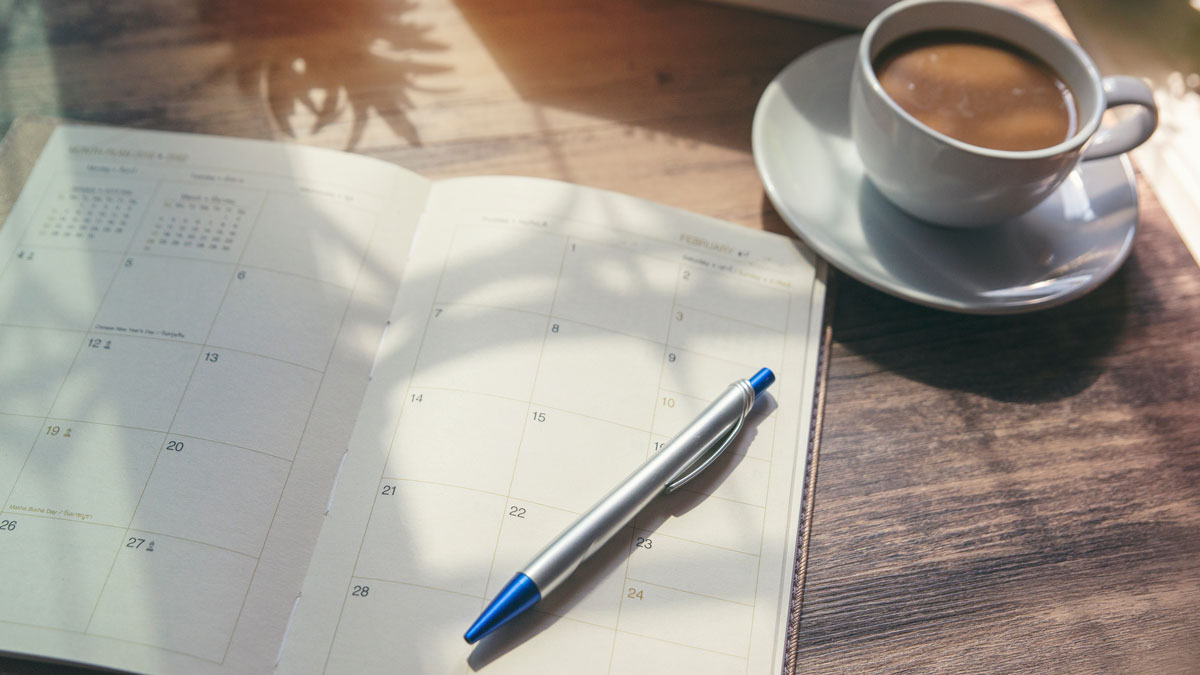 Stock image of a desk, diary, pen and coffee