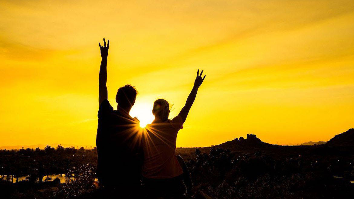 Two asu students silhouetted against a golden sunset showing the ASU pitchfork gesture