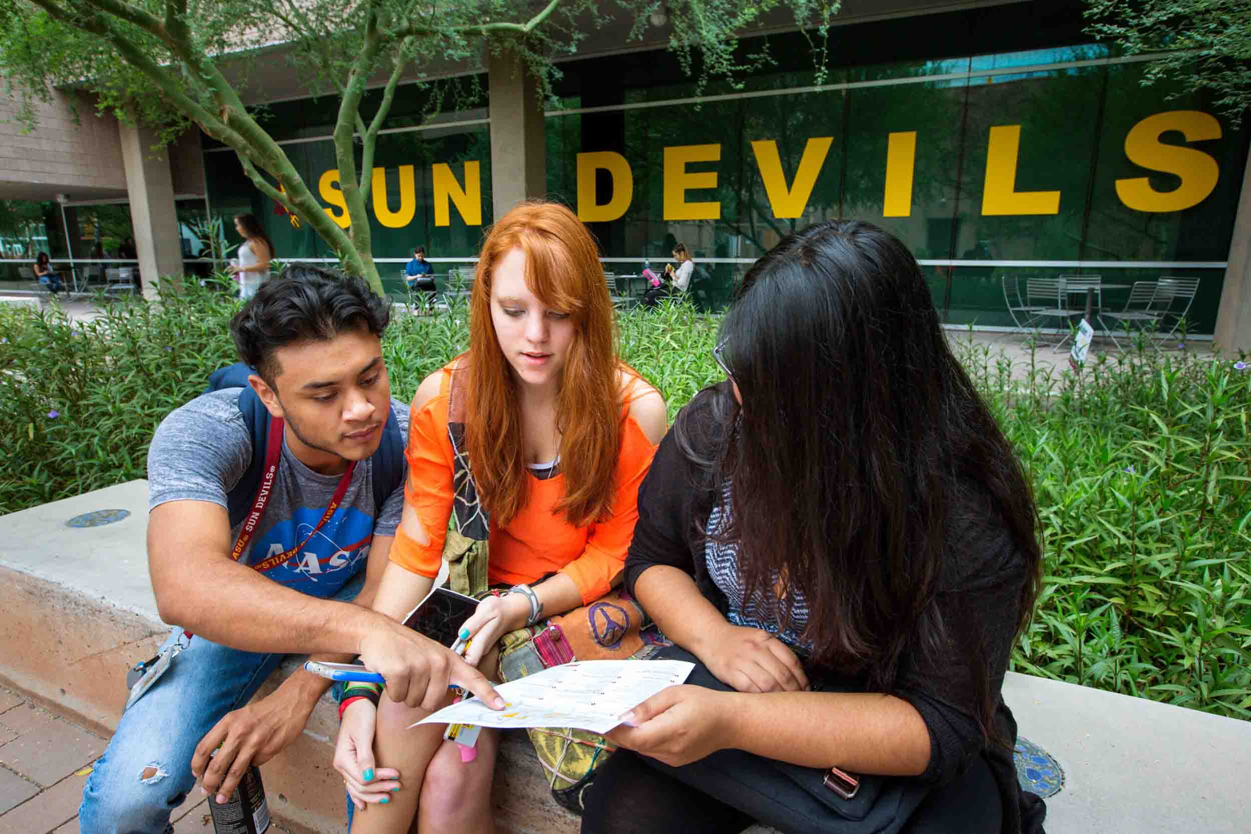 Three prospective ASU students chat together outside of an ASU building, looking over some informational materials