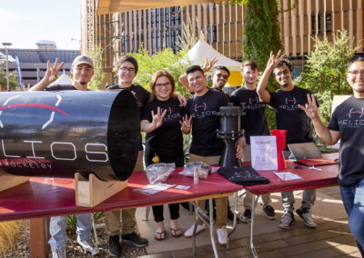 Members of the Helios Rocketry student org stand at their Fulton Schools Homecoming Block Party Exhibit