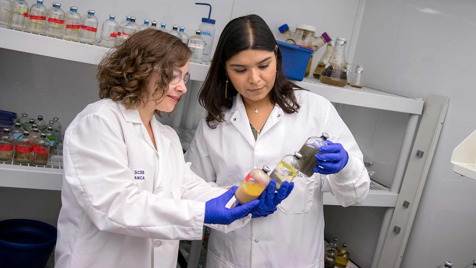 A female professor and student look at test samples together.