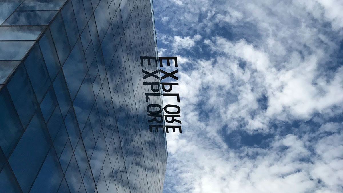 """View of an ASU building with the word """"EXPLORE"""" reflected on the mirrored glass"""